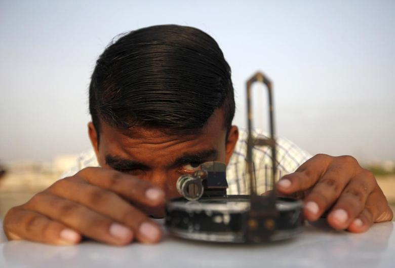 Description: C:\Users\user\Desktop\A man adjusts his compass to find the proper direction before installing a theodolite to look for the new moon that will mark the start of Ramadan in Karachi, Pakistan on June 17, 2015. Photo by Akhtar SoomroReuters.jpg